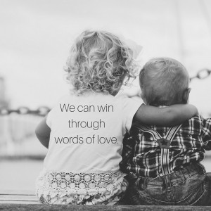 "[image description: Two toddlers sitting down, back facing camera. The older kid has arm around the younger. Text says, ""We can win with words of love."" ]"