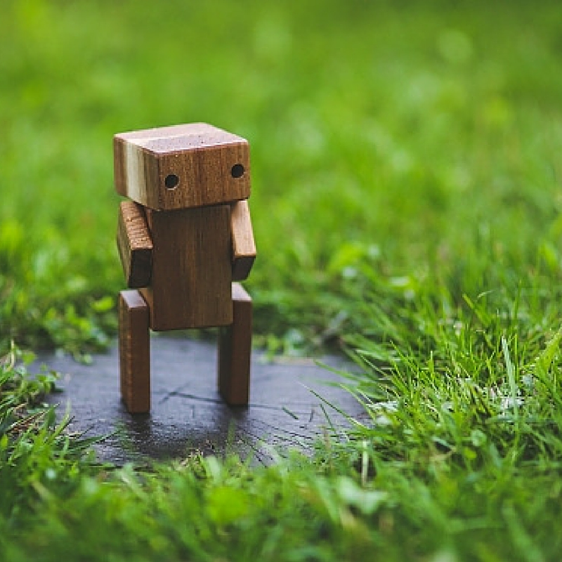 [image description: tiny wooden robot standing on some shiny surface in the middle of a grassy field]